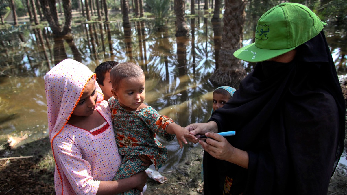 A Lady Health Worker (LHW) marks the finger of a child after administering the polio vaccine in flood-affected Bhano Goth village in Khairpur district, Sindh province