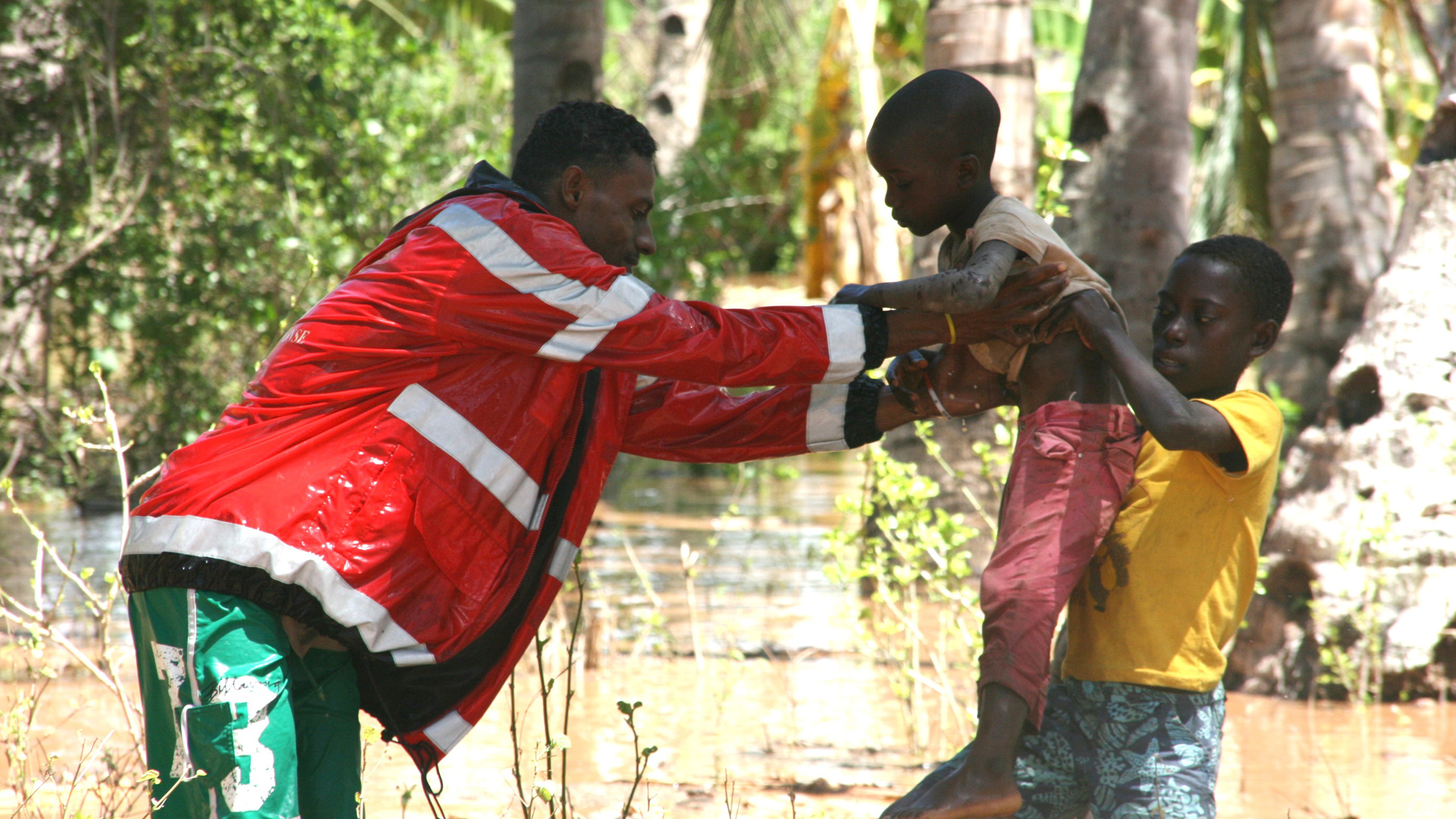 A Kenya Red Cross volunteer helps evacuate boys after heavy rains in Ganda, Malindi caused heavy flooding (Apr 2013)