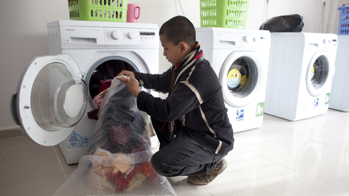 A young Syrian refugee uses the laundry services at Nizip 2 Container City, the latest of 17 Turkish camp for Syrian refugees