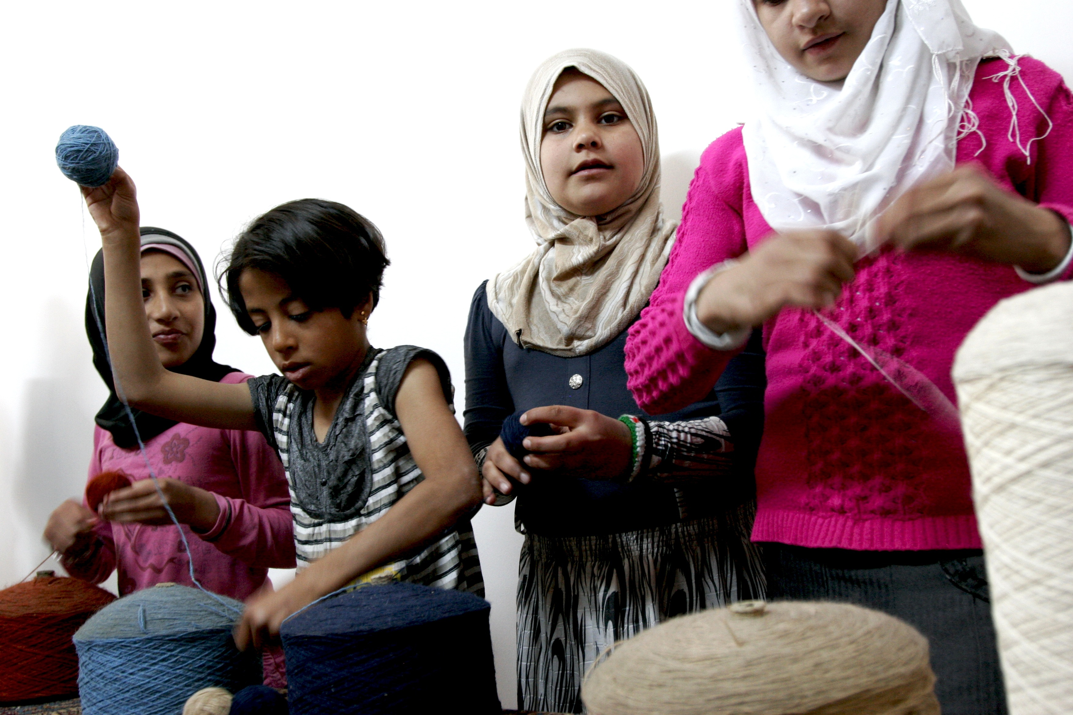 Syrian girls spool yarn for weaving into rugs in a women's-only space at Nizip Camp for Syrian refugees in southern Turkey