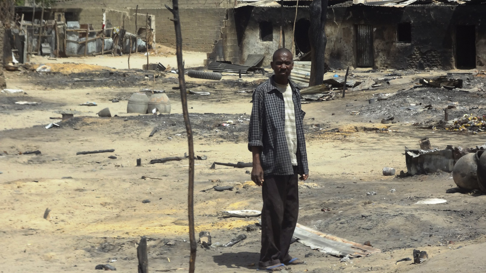 A man stands outside his destroyed home in Baga, Borno State, northeastern Nigeria, following heavy fighting between military forces from Nigeria, Niger and Chad, and Boko Haram in which some 187 people are estimated to have died