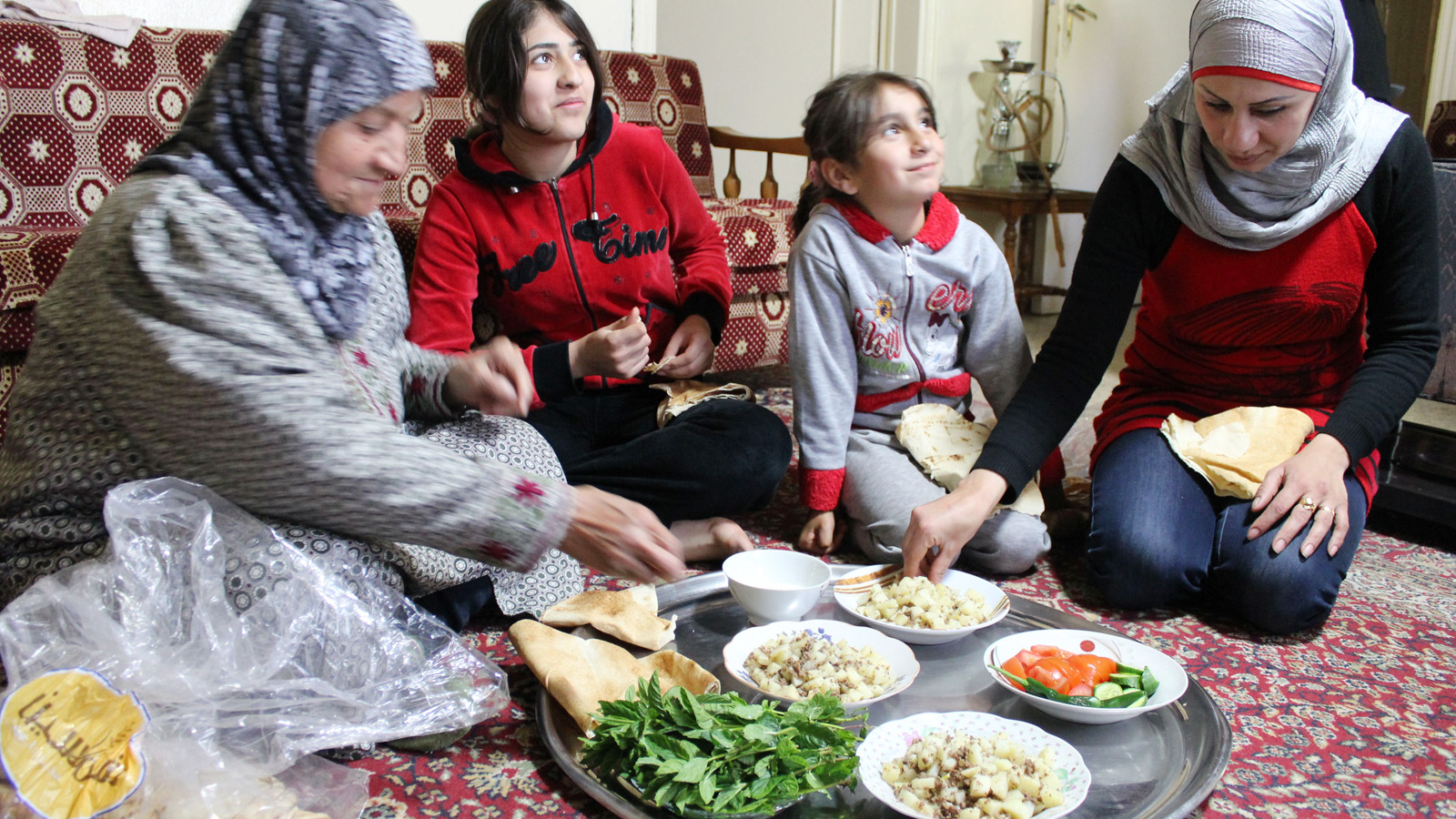 A Syrian refugee family (daughters, mother and grandmother) sit down for lunch in the home of a Lebanese family that has been hosting them for five months. At the beginning of the influx of Syrian refugees into Lebanon in 2011, the majority were hosted in