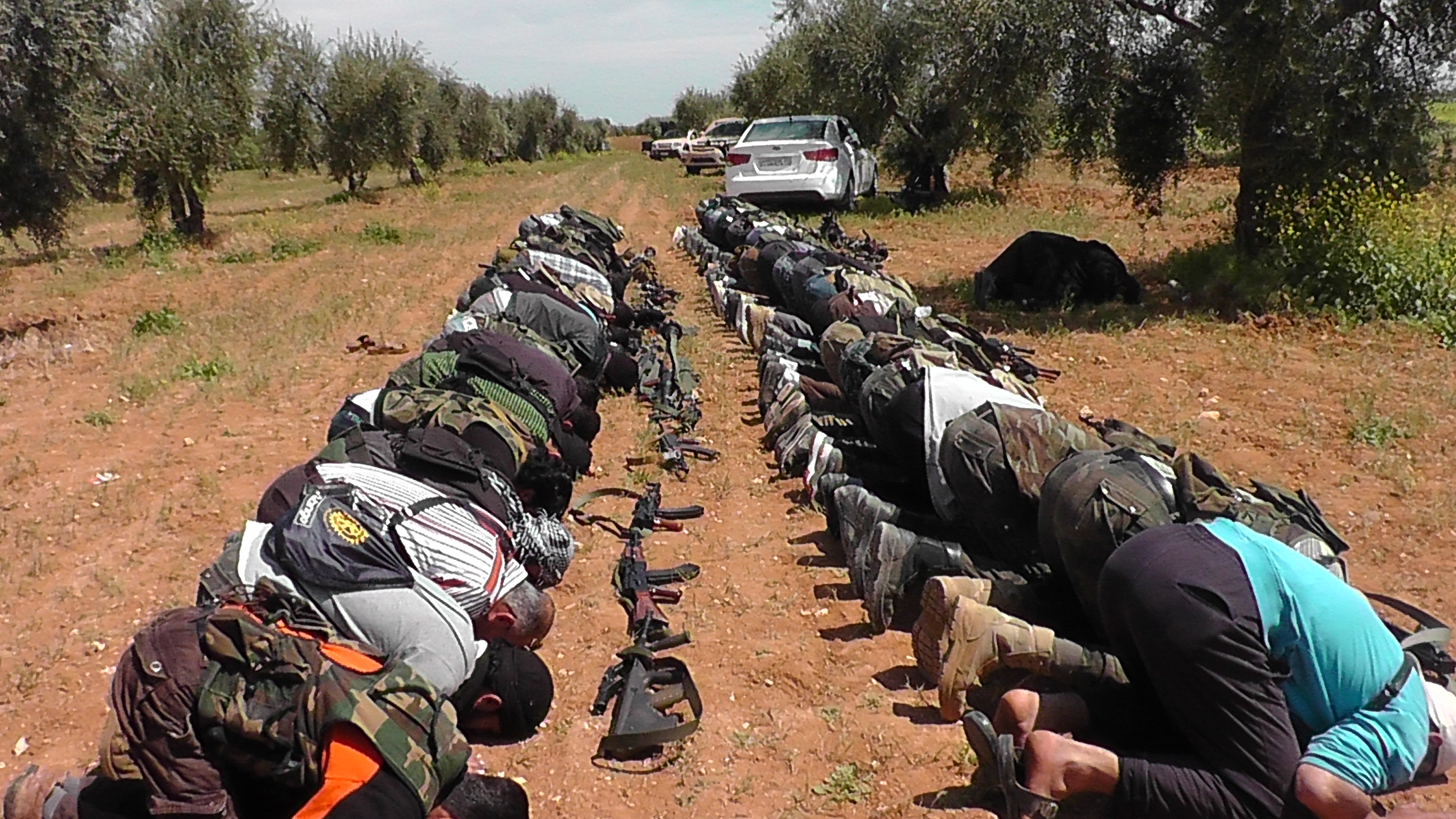Rebel fighters of the religiously conservative Liwa al Fateh Brigade of the Free Syrian Army (FSA) put their guns down for prayer near the Menagh airbase in Aleppo governorate. Syrian rebels have used a mix of religion, international humanitarian law and