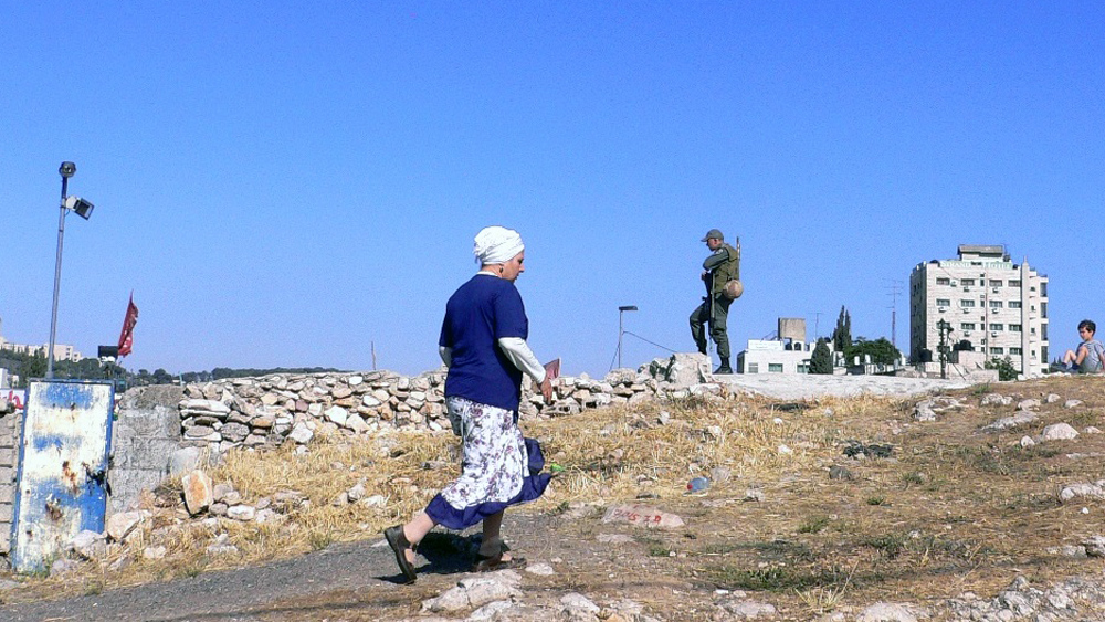 "A settler woman walks past an Israeli soldier standing guard in East Jerusalem. As Israeli settlements around the city increase, the International Crisis Group said in a recent report: ""for many Arab East Jerusalemites, the battle for their city is all"