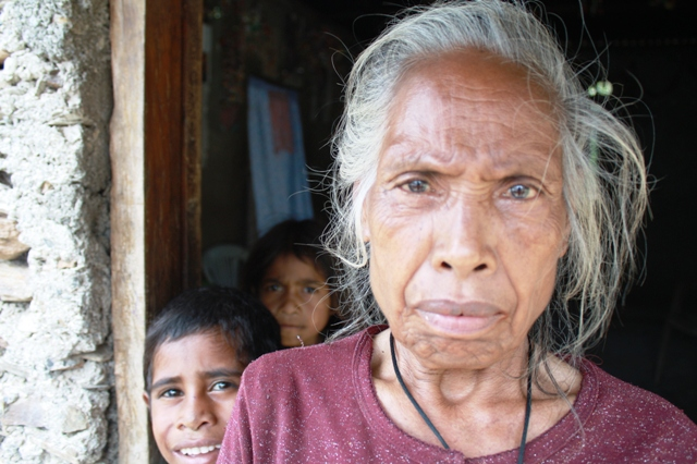 An elderly woman looks to the camera in rural Timor-Leste. In 2006, violence between gangs, members of martial arts groups, the police and the army resulted in more than 100,000 displace, many of whom sought protection in makeshift camps