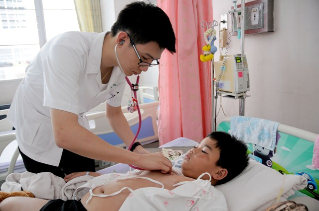 Hospital worker Teeratawat Tanawiboonchai monitors the progress of Powut Junkaw, a six-year-old dengue fever patient, at the Queen Sirikit National Institute of Child Health on 10 June. This year, Thai officials expect the largest-ever dengue fever epidem