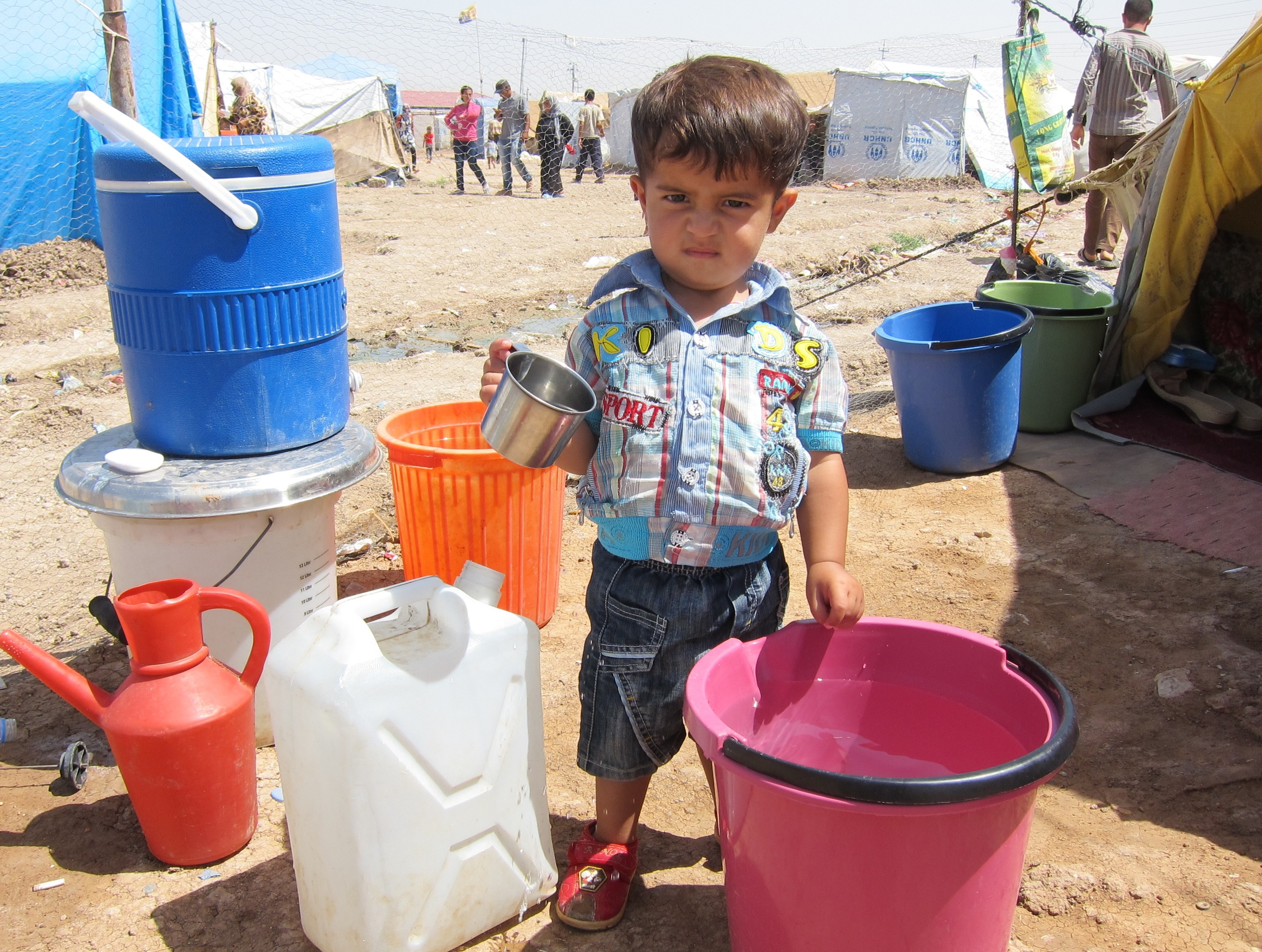 A Syrian refugee toddler plays with a bucket of water in front of his tent at Domiz camp in Iraqi Kurdistan (2013)