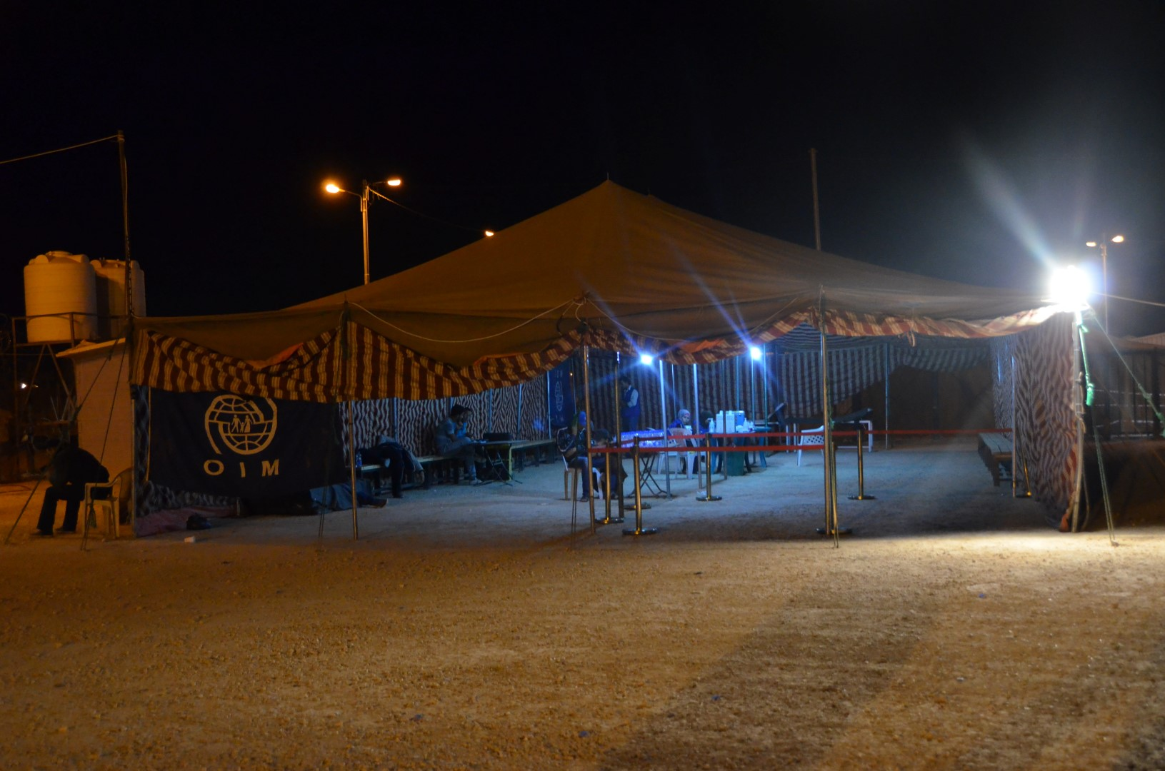 Employees of the International Organization for Migration prepare to receive hundreds of Syrian refugees in the middle of the night at the Za'atari camp in northern Jordan