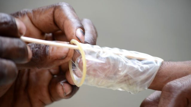 Using a popsicle stick and a condom, Simon Gosisa, 35,demonstrates how he would insert the popsicle stick under the foreskin to cut. Close to half of all men have received some form of penal cutting or another