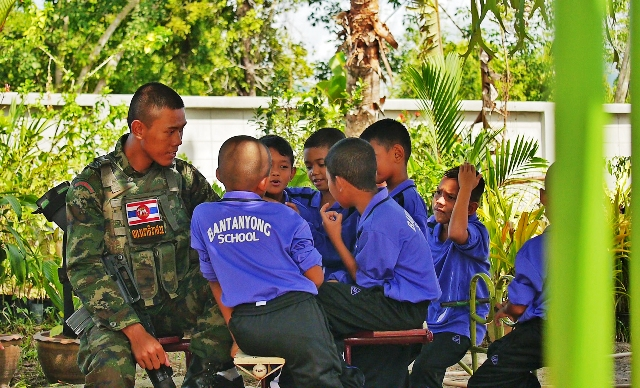 A Thai soldier talks with students at the Ban Tanyong school during his guard duty at the primary school in Naratiwat Province in Thailand's deep south