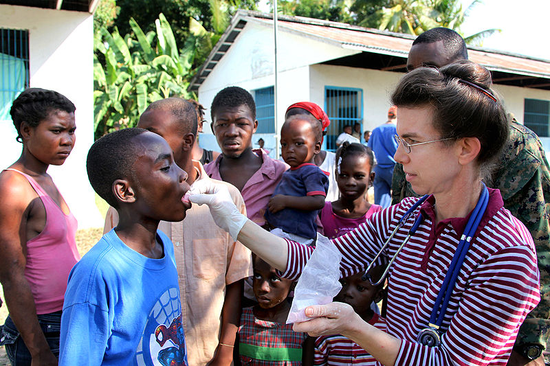Hannah McDowell, an aid worker with God's Missionary Church in Penn's Creek, Pa., administers medicine to a Haitian child in Leogane, Haiti, Jan. 24, 2010. U.S. Marines flew into the area to establish a new humanitarian aid receiving area for Haitian
