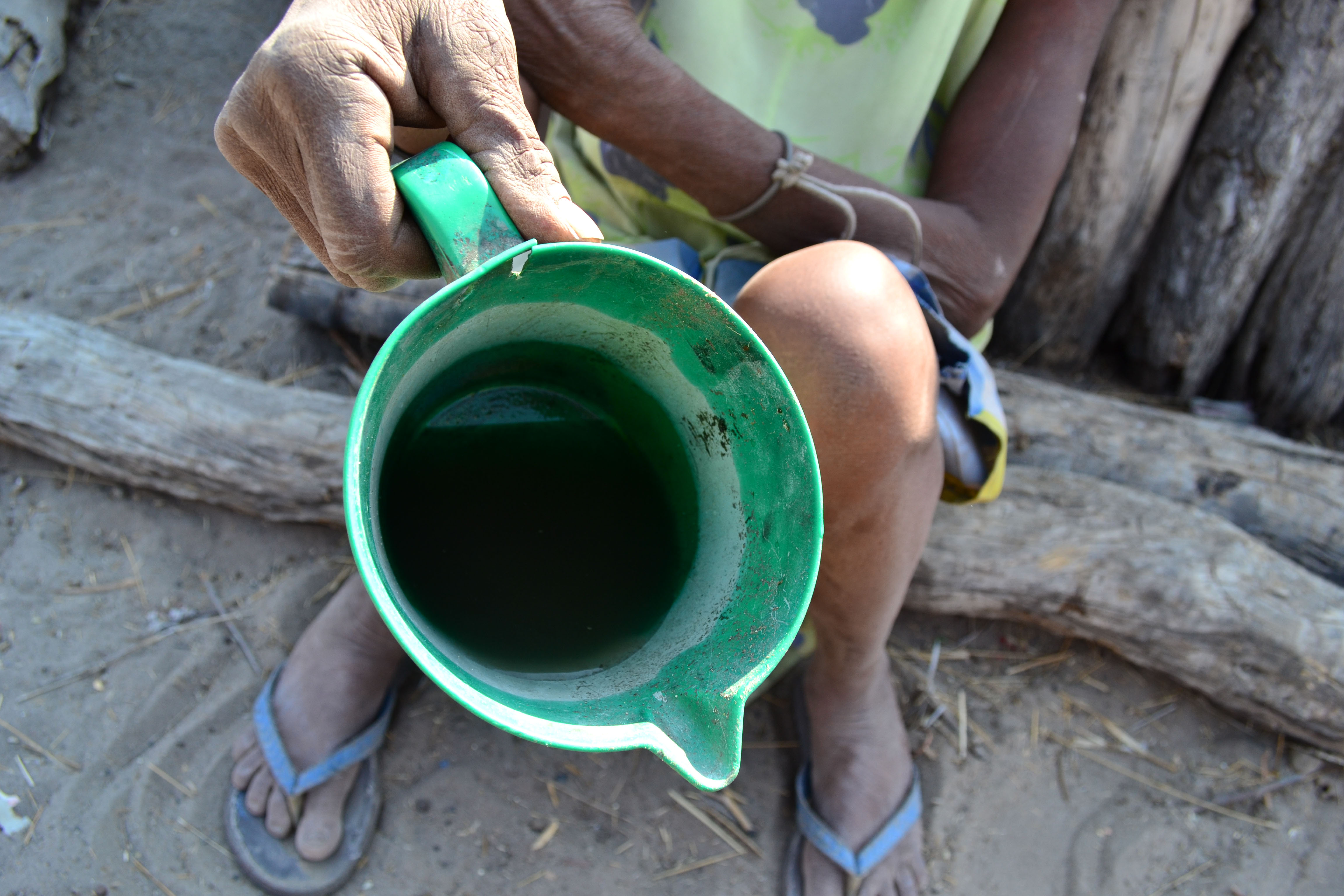 Victoria Nditondino holds up a jug of the dirty, brown water that her grandchildren have drawn from a distant well in southern Angola's Cunene Province. Lack of rain caused the nearby well to dry up months ago