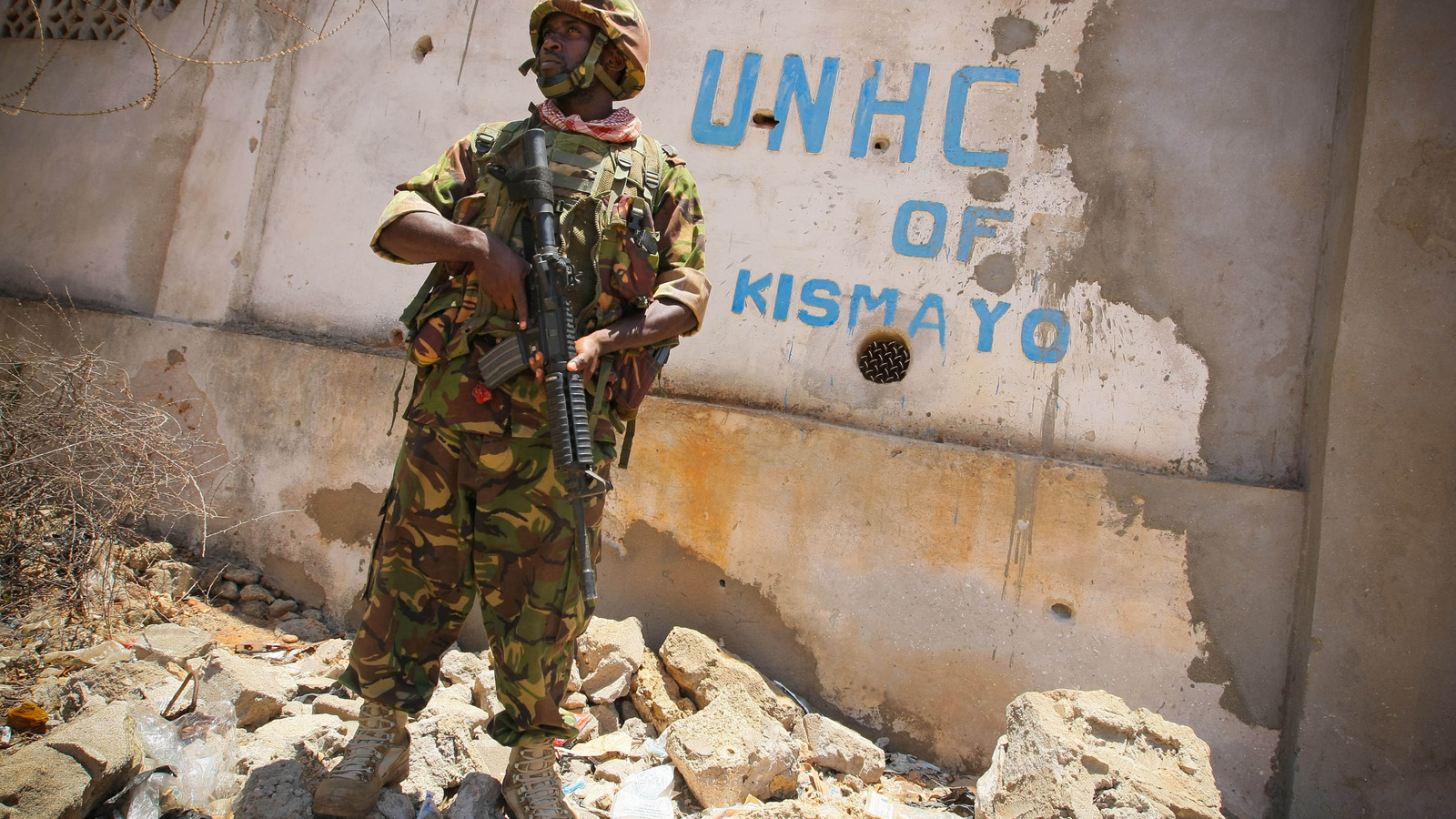 A soldier serving with the Kenyan Contingent of the African Union Mission in Somalia (AMISOM) stands guard infront of the former compound housing the offices of the United Nations High Commission for Refugees (UNHCR) while a combat engineering team sweeps