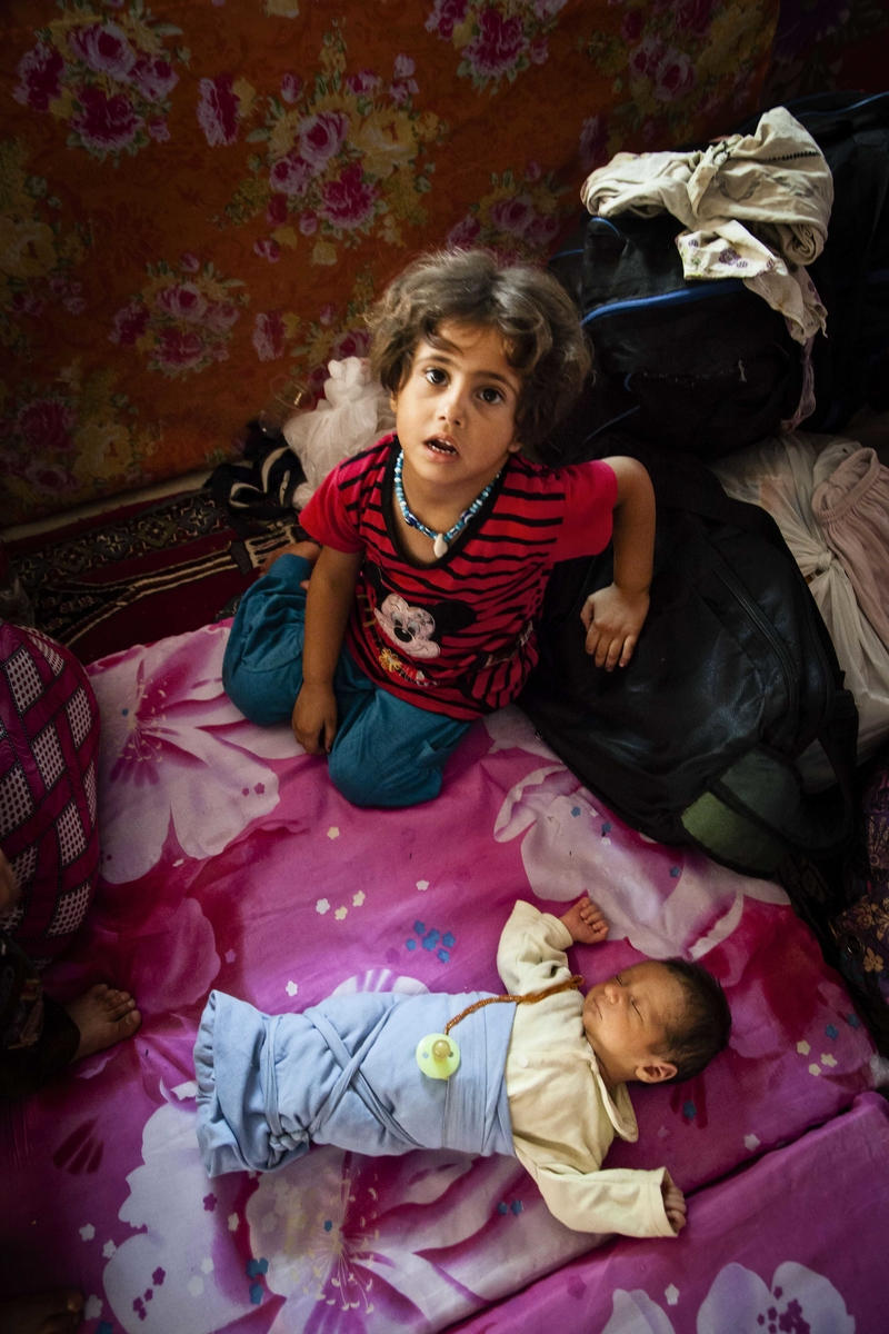 Sidra Abdul Fateh, 4, and Aziz Abdul Fateh, 10 days old, recently arrived in the semi-autonomous region of Iraqi Kurdistan after fleeing Syria. They are pictured in a mosque in the town of Arbat where they have been temporarily housed. A sudden and large