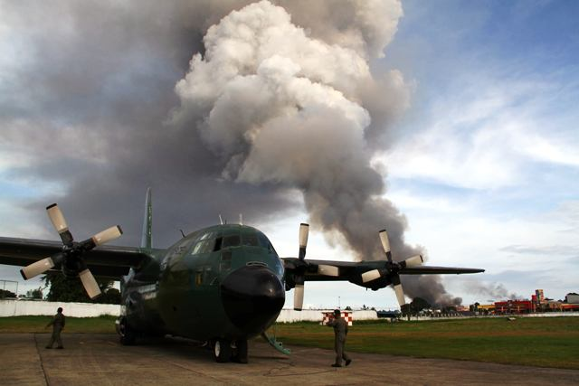 Zamboanga, Philippines - Black smoke from burning houses rises in the background as a military cargo plane bearing relief goods arrives in the besieged city of Zamboanga in Mindanao, where troops are locked in a battle with Muslim rebels opposed to peace