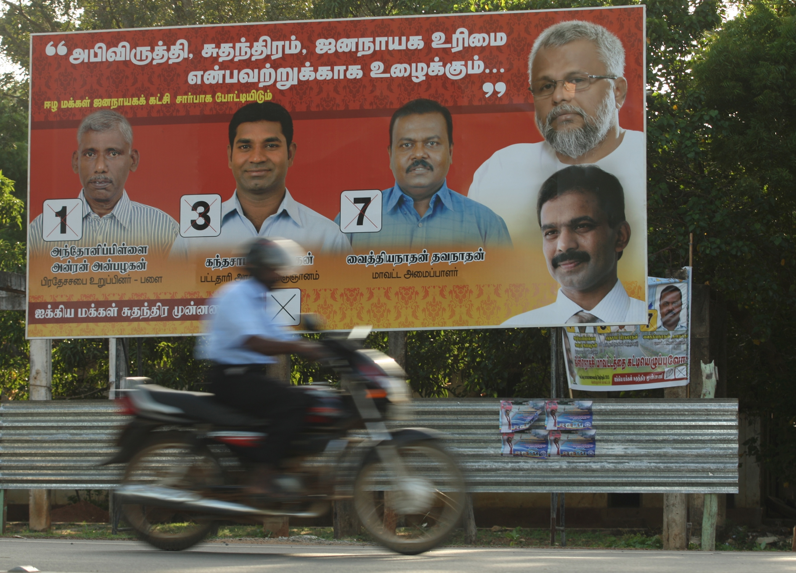 A motorcyclist rides past in the northern town of Kilinochchi an election poster of government party candidates in Northern Province's first provincial poll since fighting ended in 2009
