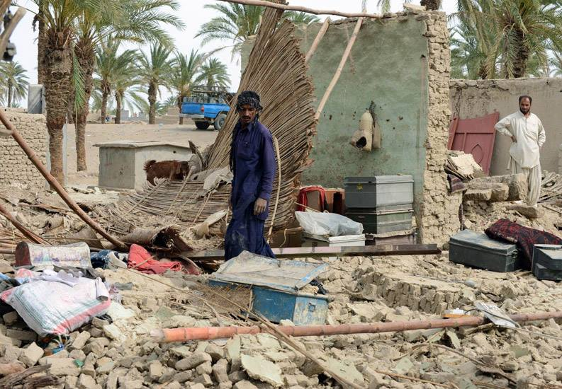 A man contemplates the remains of what was once his home after a 7.7 magnitude earthquake hit Pakistan's southwestern Balochistan province