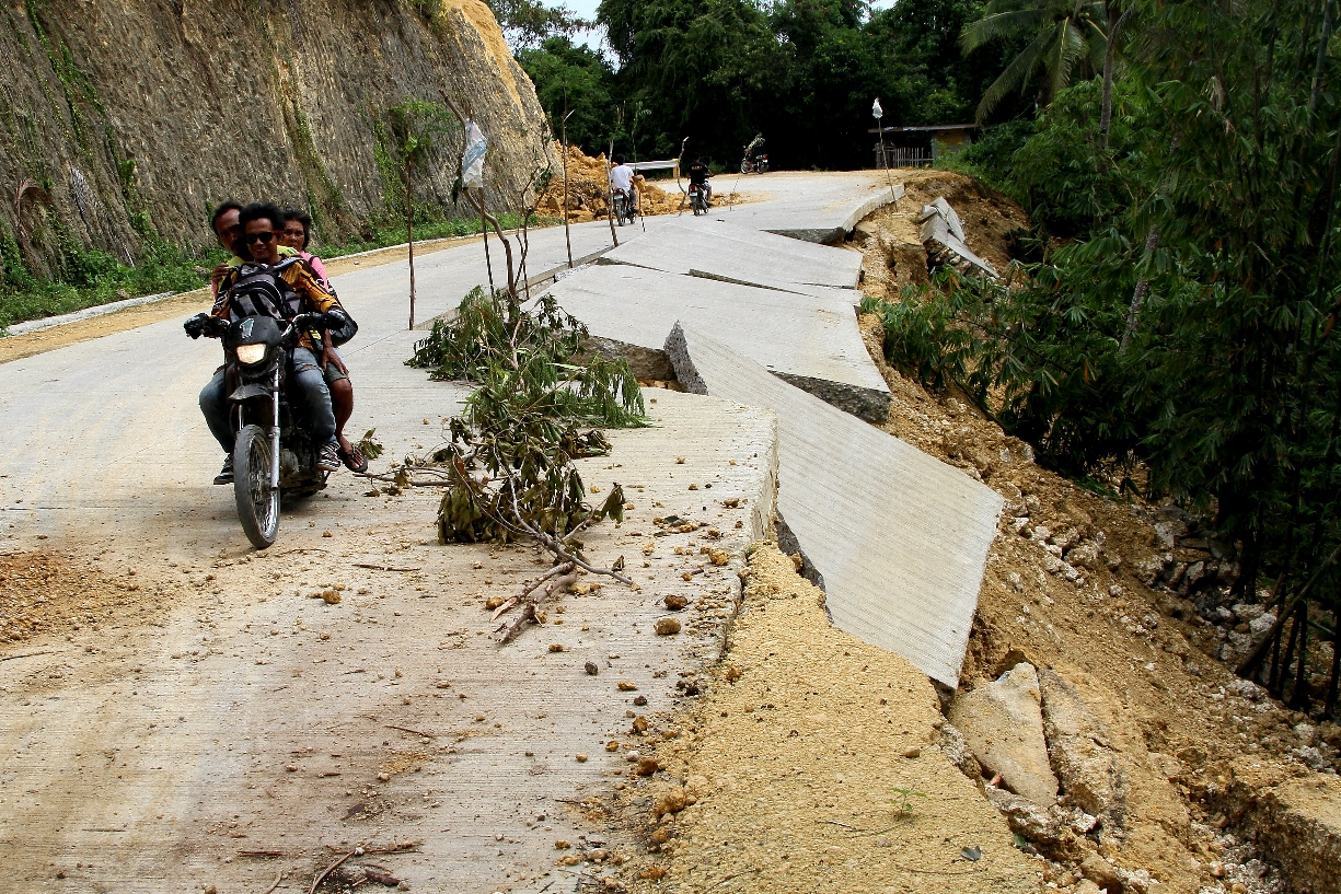 Loon, Bohol- Men on a motorcycle pass through a damaged mountain road near the town of Loon. Many roads remain impassable to other types of vehicles because they could further erode due to aftershocks