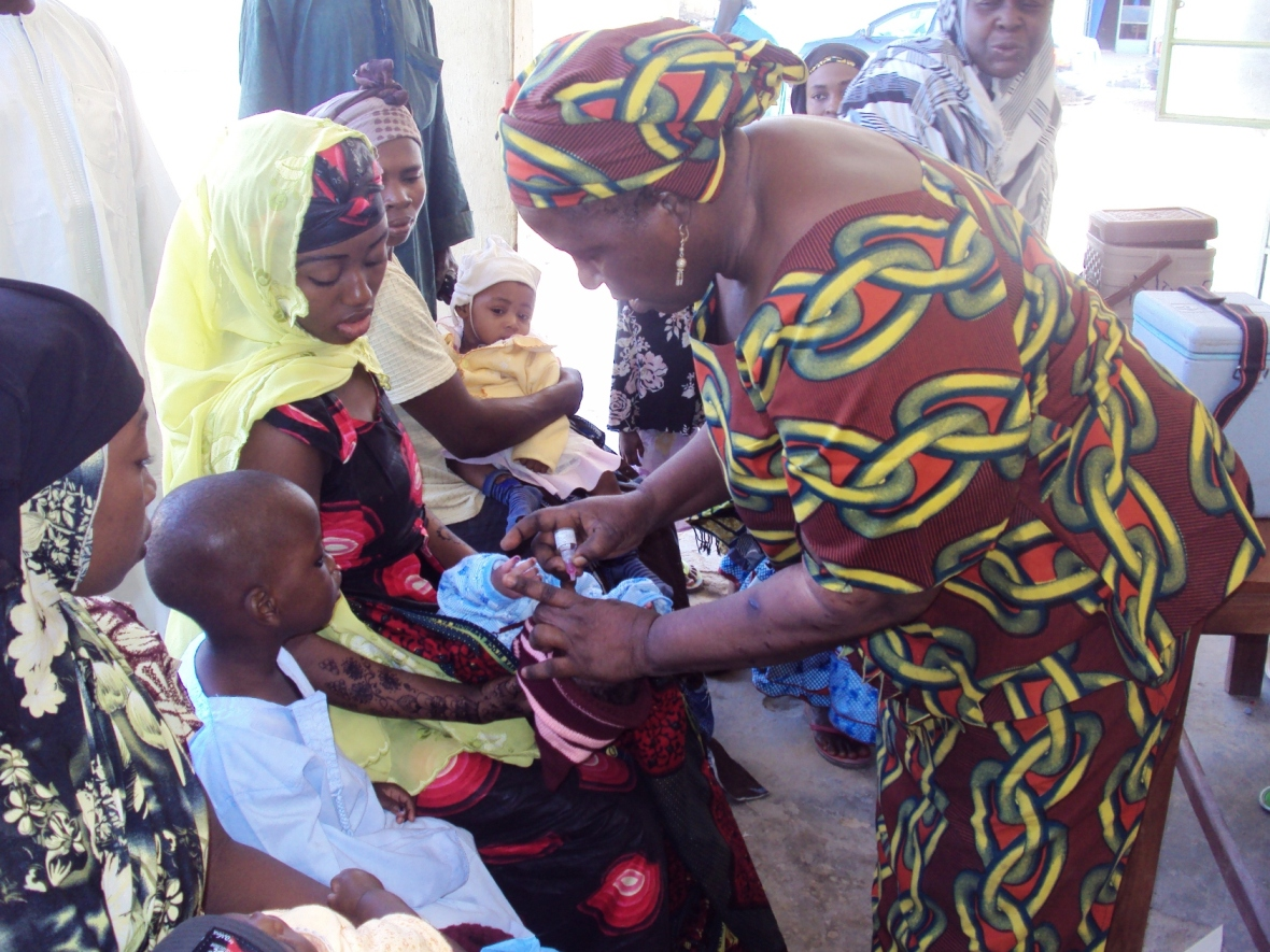 A polio vaccinator administers a polio vaccine to a child during routine immunization at a clinic in Kano, northern Nigeria (2013)