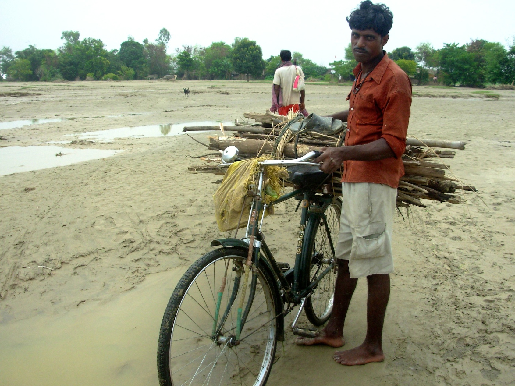 A farmer cycles near his now waterlogged farm