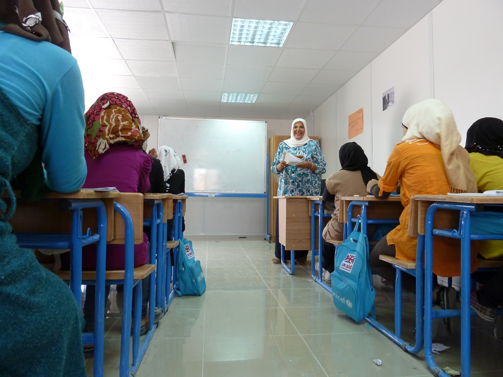 "At the ""five-star"" camp for Syrian refugees in Jordan, run by the United Arab Emirates Red Crescent (UAERC), high school pupils study English with Jordanian principal Tagit al Khijaza. The newly opened school is being run by UNICEF and supported by UK's D"