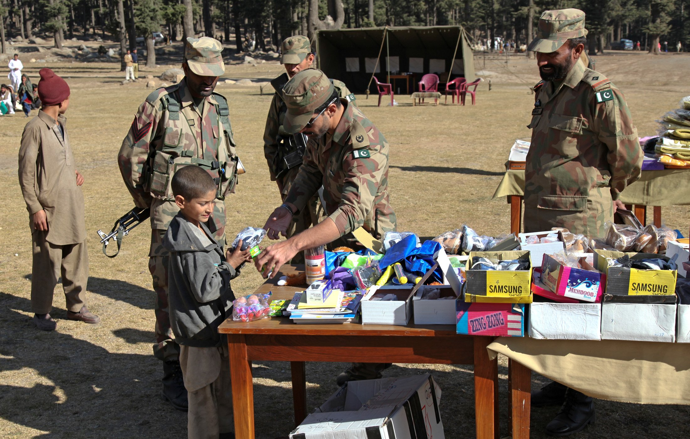 Pakistan soldiers passing out toys and shoes delivered by U.S. Army 16th Combat Aviation Brigade for flood relief in Swat Valley, Pakistan (November 24, 2010)