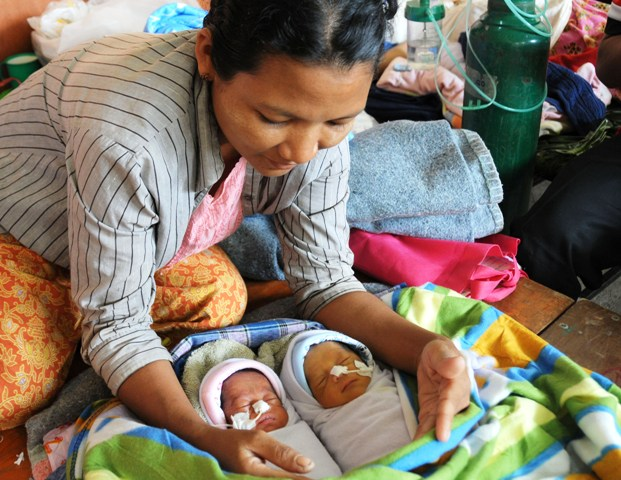 Burmese national Nin Moe Aye sits with her newborn twins who were being treated for low birth weight at a Thai clinic in Mae Sot. The country's infant mortality rate is 48 per 1,000 live births while the mortality rate for children under five is 62 per