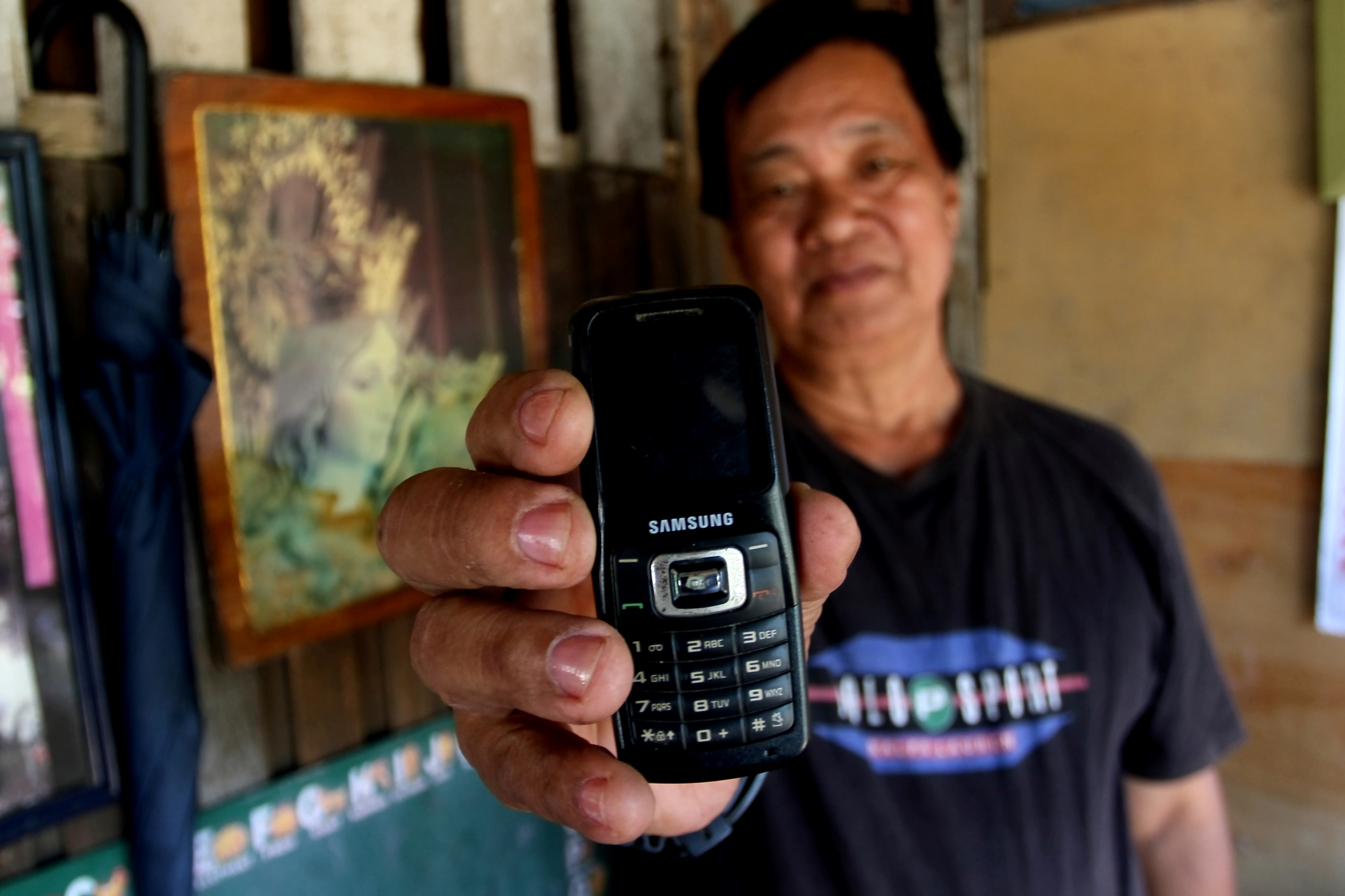Cesar Esguerra, a 60-year-old devout Catholic, shows off his mobile phone and a portrait of the Virgin Mary at his flood-damaged home in   Pasig, a suburban area east of Manila. Floods swept through much of the capital at the height of Tropical Storm Kets