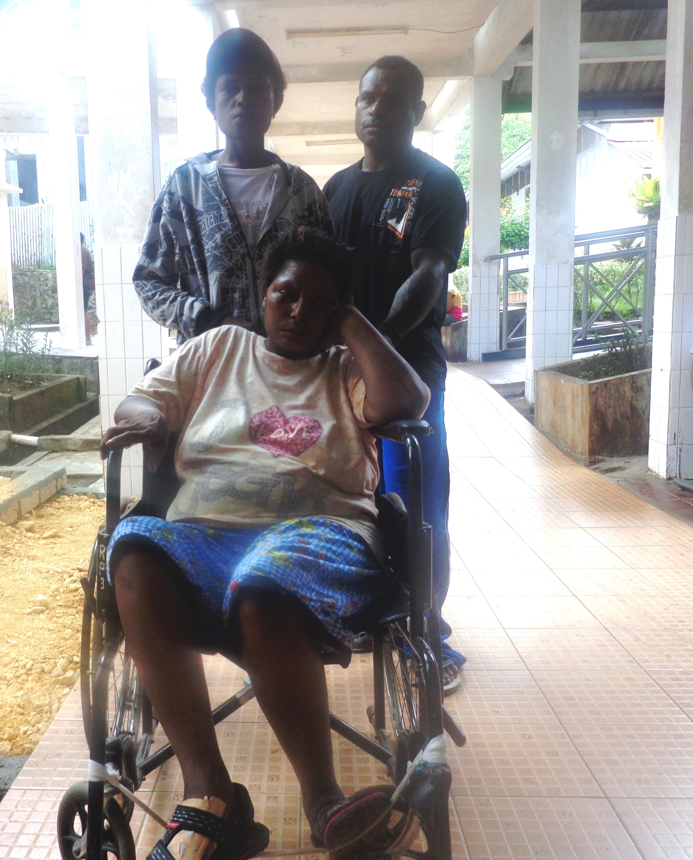 Indonesian Papuan indigenous persons qualify for health insurance under a recent government program that has swelled patient queues and hospital waiting rooms as people like Yusmina Wakum (seated in the wheelchair) take advantage of the near-free treatmen