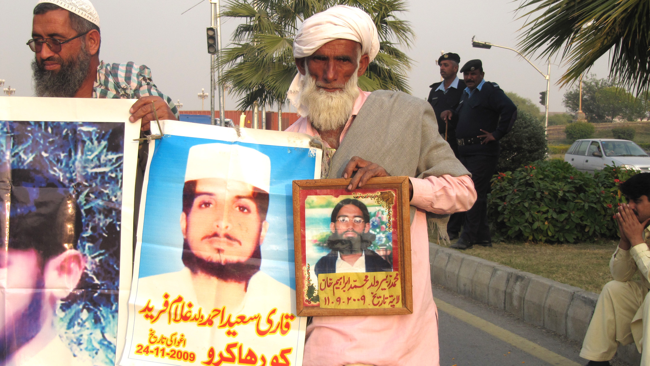 "Muhammad Ibrahim Khan, 85, from Jalalpur, Punjab, holds up pictures of his son, 18 year old Muhammad Zubair, who was picked up by security forces on 9/11/2009. ""He was our only child, and was just married,"" Khan said. ""At least tell us what he was c"