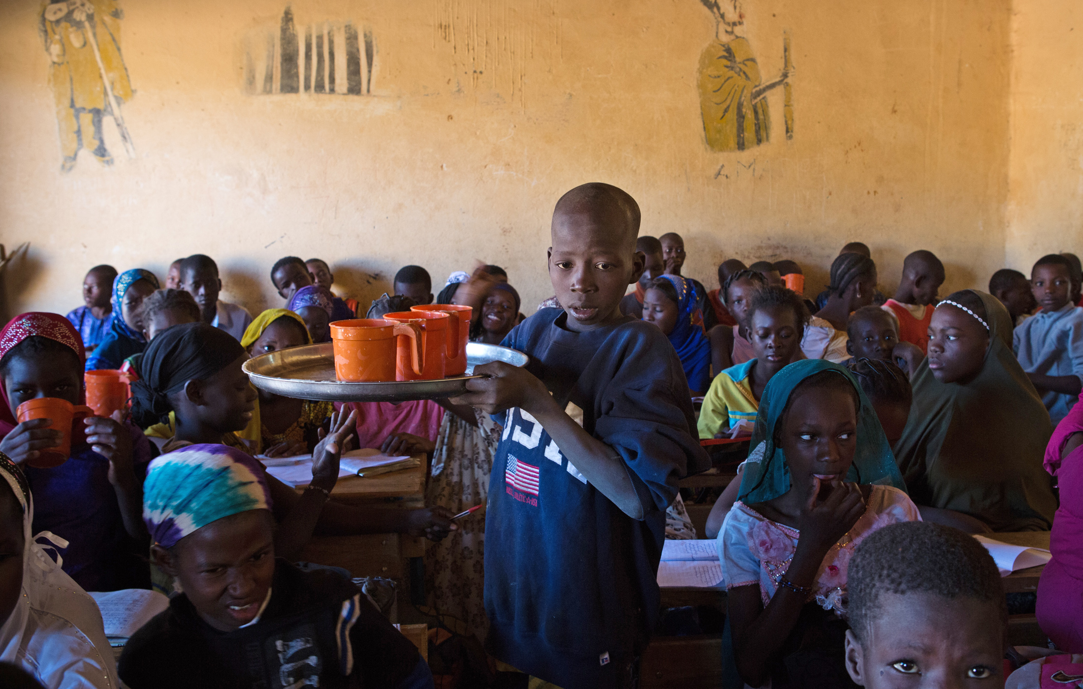 A student hands out meals to his fellow classmates in Gao, Mali. The World Food Program provides two meals a day to schools in Gao and other conflict-affected cities in northern Mali, such as Timbuktu. The emergency feeding program has seen a rise in atte