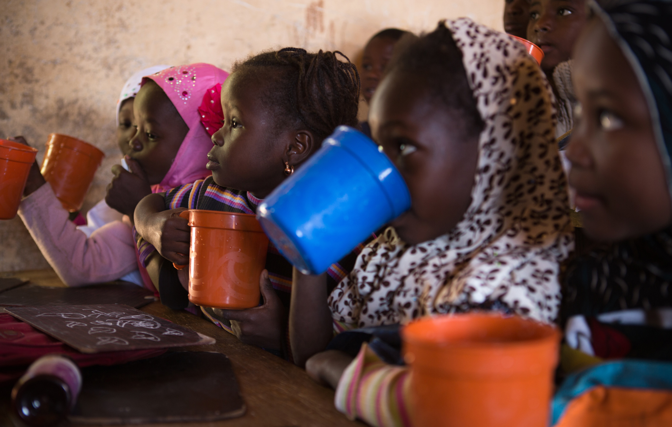 Students eat their first meal of the day in their classroom in Gao, Mali. The World Food Program provides two meals a day to schools in Gao and other conflict-affected cities in northern Mali, such as Timbuktu. The emergency feeding program has seen a ris