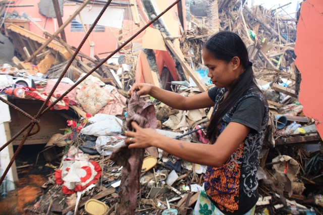 A young woman sifts through the wreckage of her home in the town of Palo, which was devastated by Typhoon Haiyan on 8 November 2013