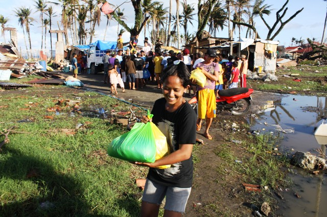 A young woman receives assistance in the typhoon-devastated town of Santa Rosa in Southern Leyte Province. More than 4 million people were displaced in the aftermath of Typhoon Haiyan, which slammed into the central Philippines on 8 November 2013
