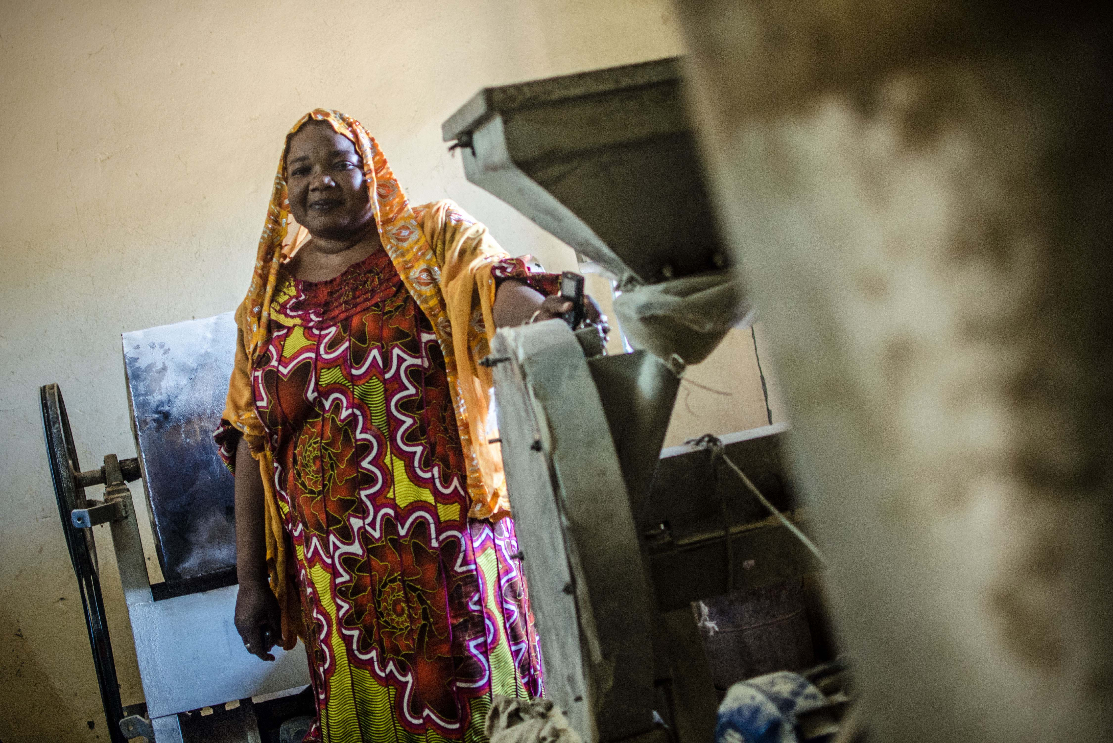 Guindo Tembely, director of the NGO, YAGTU, stands behind machinery used to make Farine, a protein rich dietary supplement given to women and children in Mali's Mopti region.