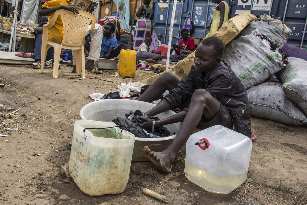 A teenager displaced by recent violence washes clothes in a basin at the compound of the UN Mission in South Sudan (UNMISS), which has become a makeshift camp for Nuer people.