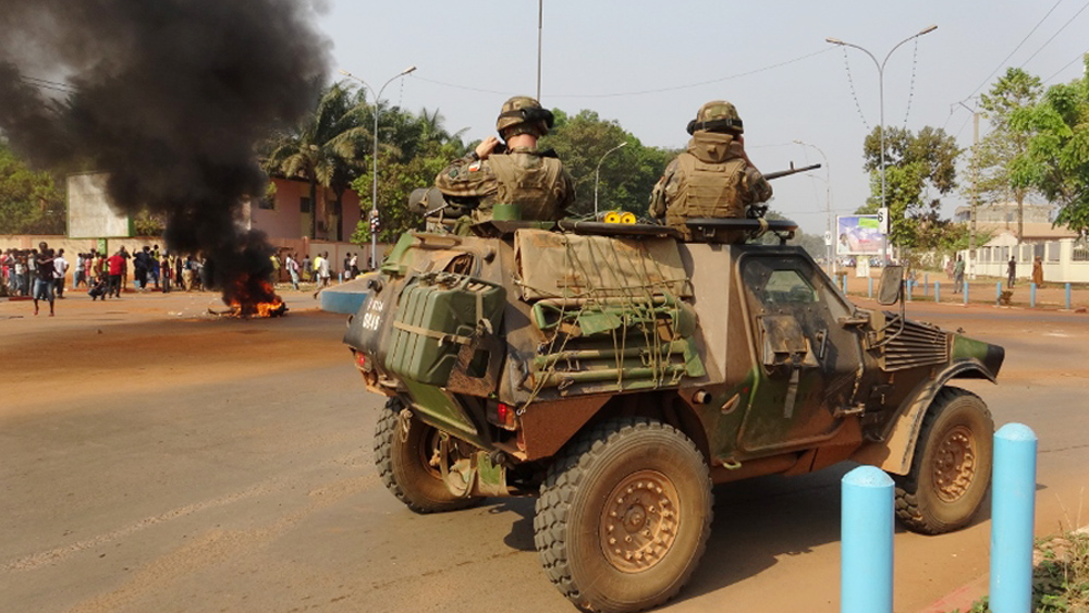 French troops patrol a street in Bangui as the body of a man lynched by a mob burns in the distance.