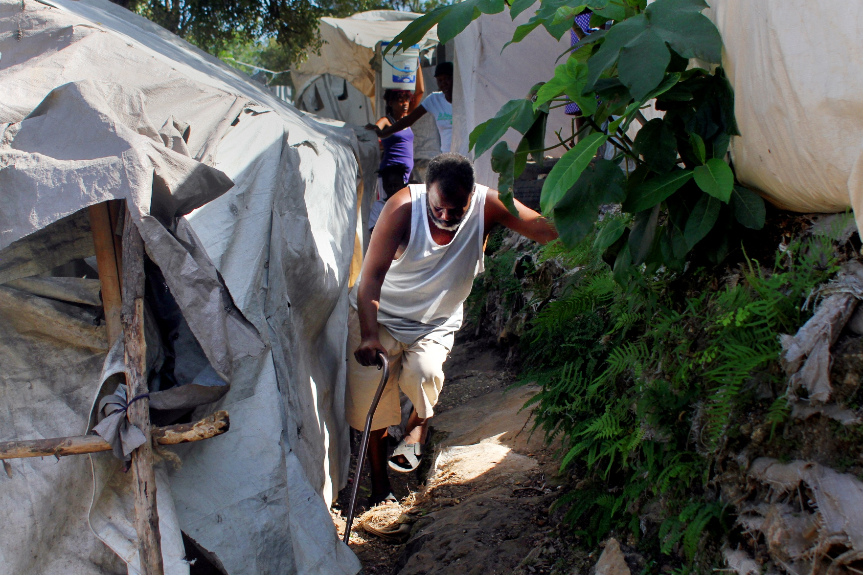 Charles Ivalien, 52, makes his way through the narrow, hillside paths of the Acra 2 camp in the Pétion-Ville commune of Port-au-Prince. The International Organization for Migration is in the process of clearing the camp, one of 271 still open since the 2