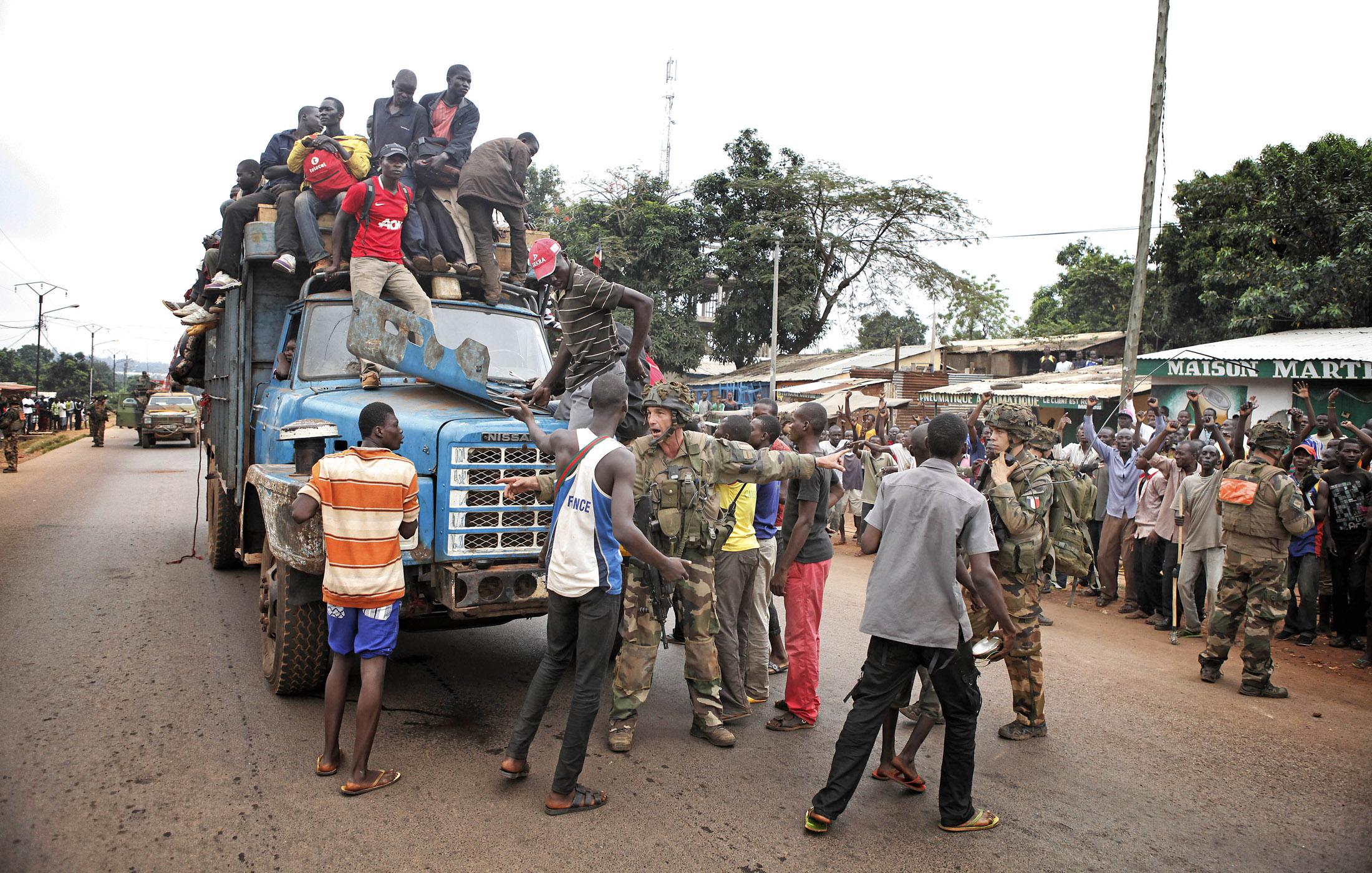 French soldiers protect a convoy of fleeing refugees from an angry mob in the Bangui estate of PK. Many muslims have fled the ongoing violence in Bangui
