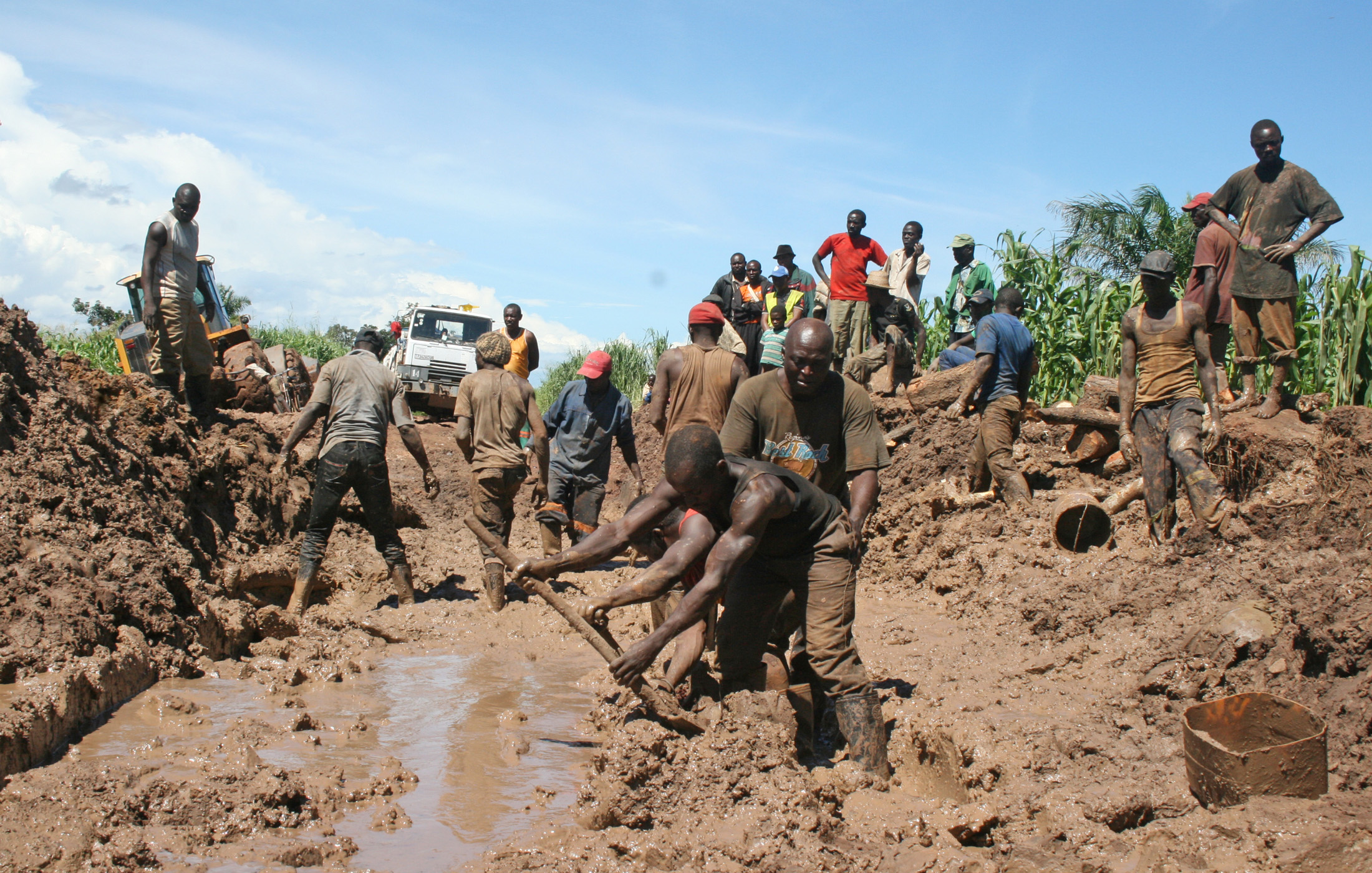 Truck crews work on a muddy road in an attempt to make it passable in DRC's Katanga province