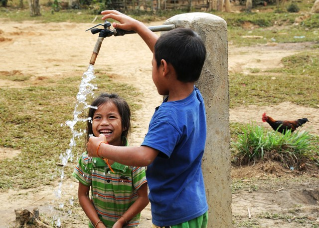 Lao children collect water from a public standpipe shared by their rural village