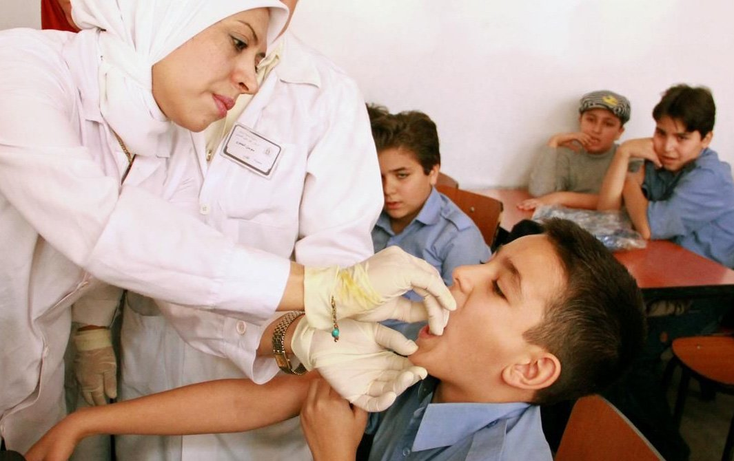 A boy in Grade 6 receives a dose of vitamin A from a health worker, who has also given him a measles, mumps and rubella (MMR) vaccination, at a school in Damascus, the capital, on the first day of the UNICEF-supported nationwide polio and MMR immunization
