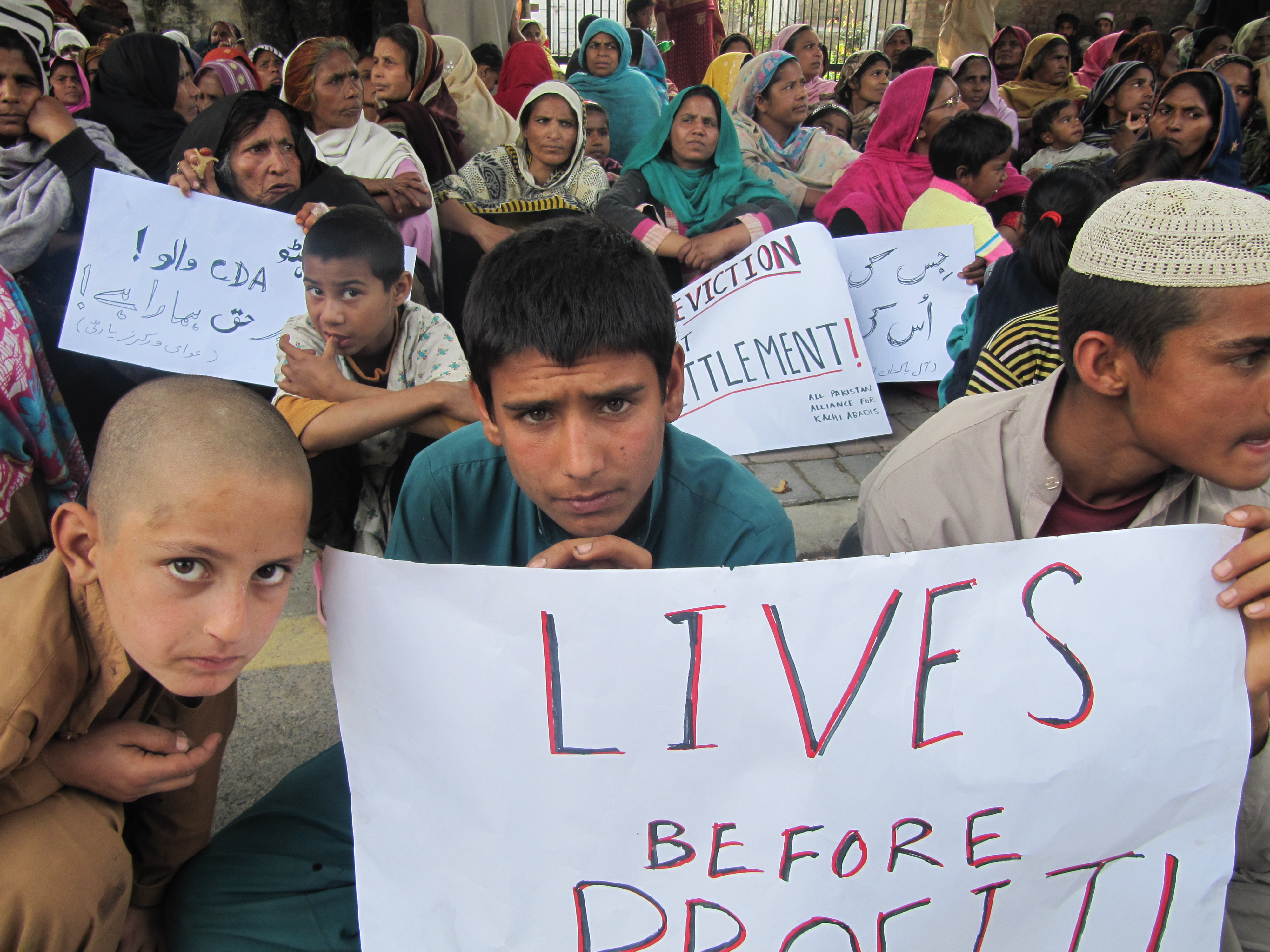 Ghaffar Ali, 14 (center) attends a protest against evictions of slums in Pakistan.  Ghaffar sells vegetables from a cart in the capital Islamabad's main produce market.  He says his family is from Bajaur Agency, but has lived in Afghan Basti, a nearby slu