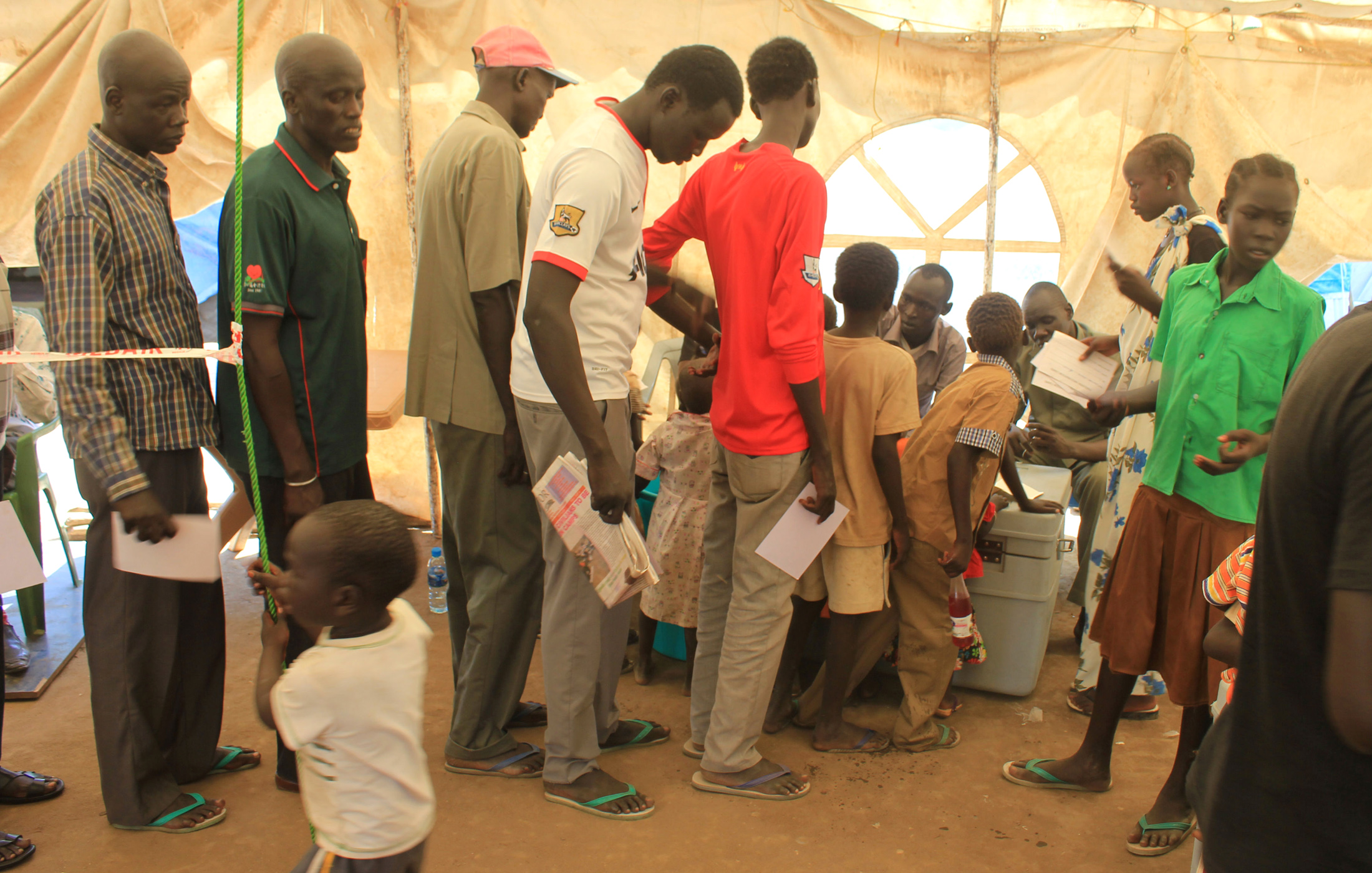 Residents of the Tomping camp in Juba wait in line for a cholera vaccination