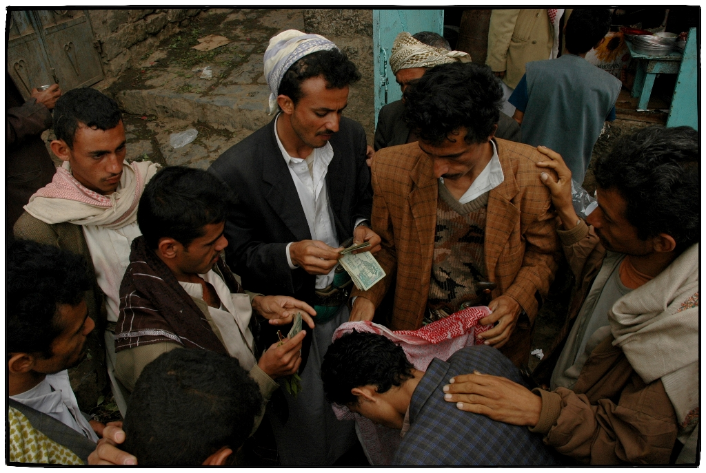 Men exchange money in Yemen. For generic use