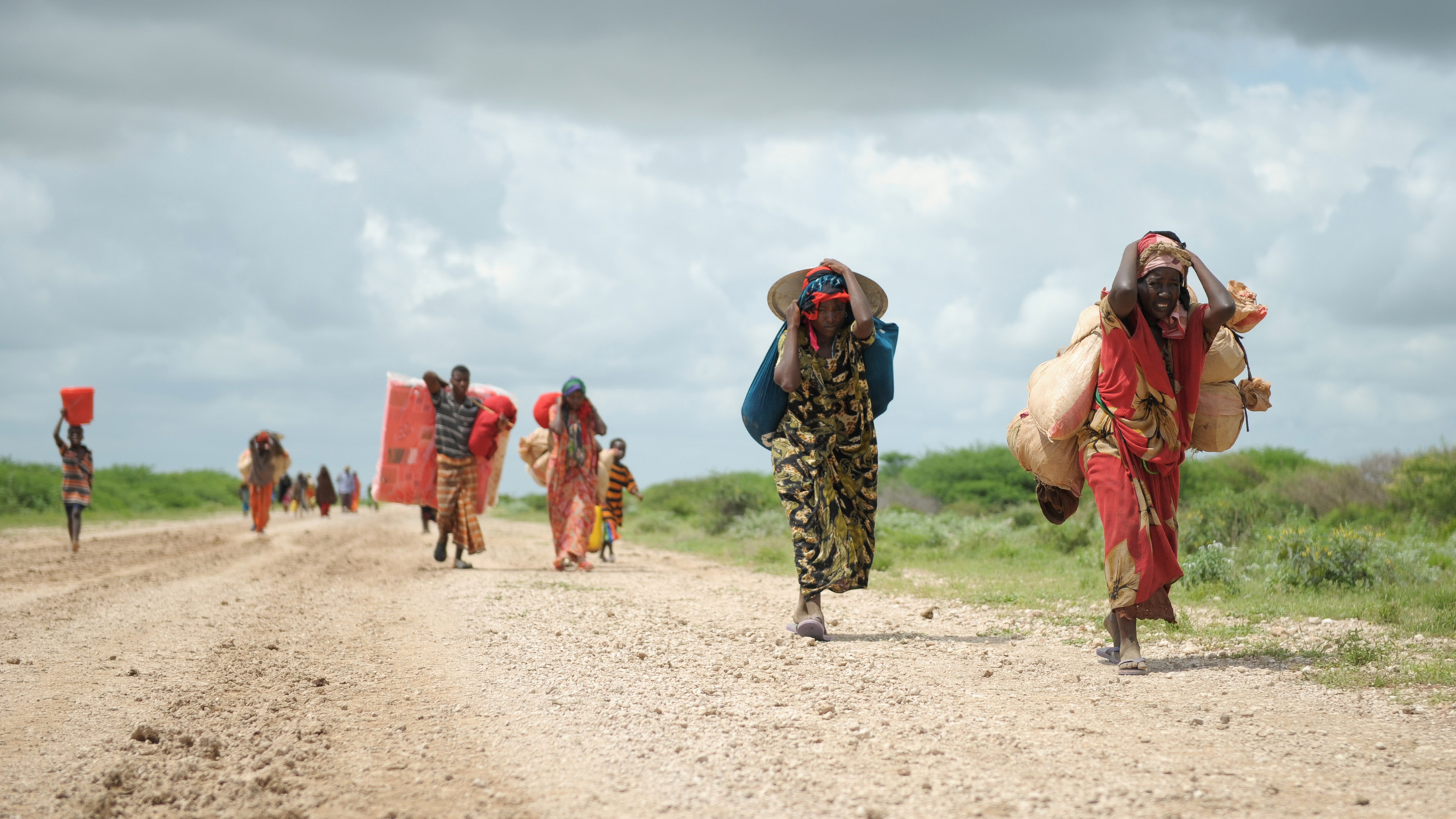 Carrying whatever possessions they can, women arrive in a steady trickle at a camp for Internally Displaced People (IDPs) established next to a base of the African Union Mission for Somalia (AMISOM) near Jowhar.