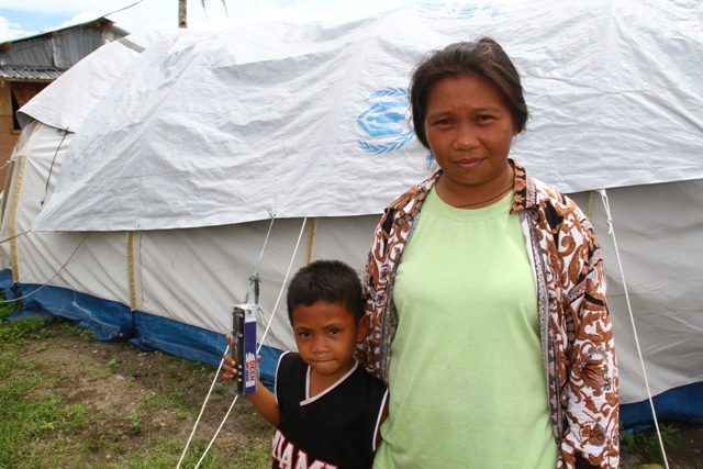 Arlyn Redona, 32 and her son Michael, 5, outside their tent six months after Typhoon Haiyan struck. More than 2 million remain without adequate shelter six months after the category 5 storm stuck on 8 November, 2013