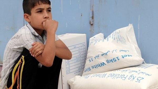 An Iraqi boy receives assistance from the World Food Program (WFP) after flooding in Abu Ghraib in April 2014, caused by militants of the Islamic State of Iraq and the Levant (ISIL) who took control of the Nuaimiyah dam.
