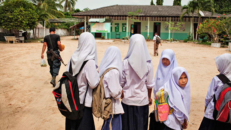 A paramilitary Ranger with groceries walks by students at Pakaluesong Elementary School in southern Thailand. About 30 Rangers live in a camp established in the school grounds.