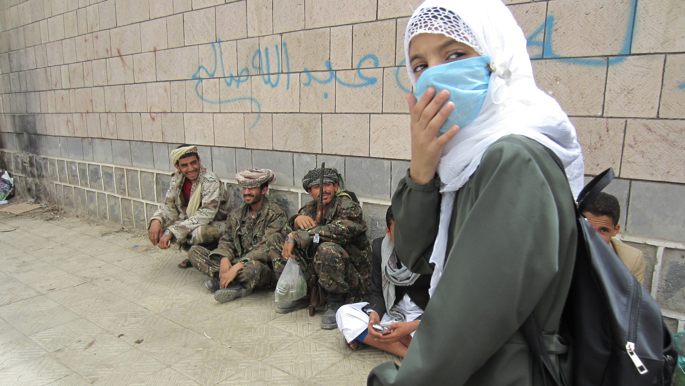 A girl student leaves al-Furadh School at the end of the day in Yemen. Soldiers relax and chew qat outside the school walls. They lived in third-floor classrooms for several months, students and teachers said.